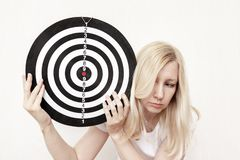 Woman holding a dart board in hands close up, aiming and targetting concept stock photo
