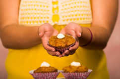 Woman holding delicious brown colored muffin with cream topping, showing to camera, pastry concept.  Stock Image
