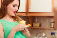 Woman holding delicious sweet cake. Gluttony. Royalty Free Stock Image