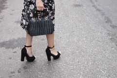 A woman holding a designer clutch purse and wearing high heels Royalty Free Stock Photography