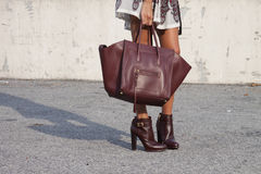 A woman holding a designer handbag and wearing booties. Street style during new york fashion week royalty free stock image