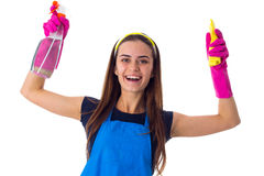 Woman holding detergent and duster. Smiling young woman in blue T-shirt and apron with pink gloves holding yellow duster and detergent on white background in Stock Photos