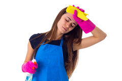 Woman holding detergent and duster. Tired young woman in blue T-shirt and apron with pink gloves holding duster and detergent on white background in studio Royalty Free Stock Photo