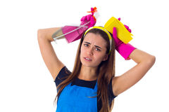 Woman holding detergent and duster. Tired young woman in blue T-shirt and apron with pink gloves holding yellow duster and detergent on white background in Royalty Free Stock Images