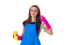 Woman holding detergent and duster. Young attractive woman in blue T-shirt and apron with pink gloves holding yellow duster and detergent on white background in Royalty Free Stock Photography