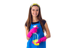 Woman holding detergent and duster. Young charming woman in blue T-shirt and apron with pink gloves holding yellow duster and detergent on white background in Stock Photography