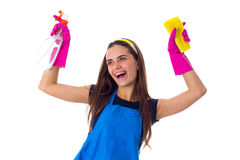 Woman holding detergent and duster. Young funny woman in blue T-shirt and apron with pink gloves holding yellow duster and detergent on white background in Stock Photos