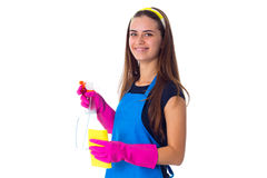 Woman holding detergent and duster. Young happy woman in blue T-shirt and apron with pink gloves holding yellow duster and detergent on white background in Stock Image