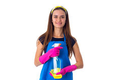 Woman holding detergent and duster. Young nice woman in blue T-shirt and apron with pink gloves holding yellow duster and detergent on white background in studio Stock Photography