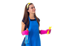 Woman holding detergent and duster. Young pleasant woman in blue T-shirt and apron with pink gloves holding yellow duster and detergent on white background in Royalty Free Stock Images