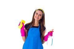 Woman holding detergent and duster. Young positive woman in blue T-shirt and apron with pink gloves holding yellow duster and detergent on white background in Stock Photo