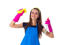 Woman holding detergent and duster. Young pretty woman in blue T-shirt and apron with pink gloves holding yellow duster and detergent on white background in Stock Photos