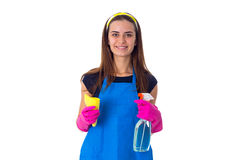 Woman holding detergent and duster. Young smiling woman in blue T-shirt and apron with pink gloves holding yellow duster and detergent on white background in Stock Photography