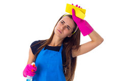 Woman holding detergent and duster. Young tired woman in blue T-shirt and apron with pink gloves holding duster and detergent on white background in studio Royalty Free Stock Image