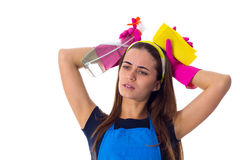 Woman holding detergent and duster. Young tired woman in blue T-shirt and apron with pink gloves holding yellow duster and detergent on white background in Royalty Free Stock Images