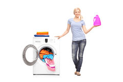 Woman holding detergent next to a washing machine Stock Images