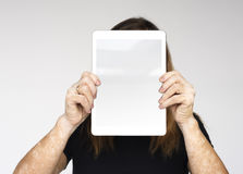 Woman is holding a digital device on her face stock photo