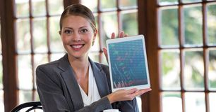 Woman holding digital tablet against window in background Royalty Free Stock Images