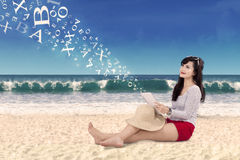 Woman holding digital tablet at bach Stock Images