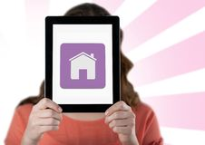 Woman holding digital tablet with home icon in front her face. Against white pink background royalty free stock photography