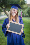 Woman Holding Diploma and Blank Chalkboard Wearing Cap and Gown Stock Images