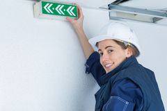 Woman holding directional exit arrow sign on wall. Exit royalty free stock photos