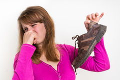 Woman holding dirty stinky shoes. Unpleasant smell concept Royalty Free Stock Images