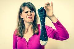 Woman holding dirty stinky socks - retro style. Woman holding dirty stinky socks - unpleasant smell concept - retro style royalty free stock image