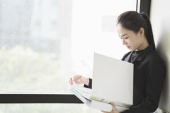 Woman holding document files beside a window. Asian Business woman holding document files beside a window royalty free stock image