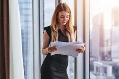 Woman holding documents, looking through papers, studying the report standing near window with view on skyscrapers royalty free stock photo