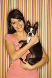 Woman holding dog. Young adult female Caucasian holding Boston Terrier dog on striped background Royalty Free Stock Photography