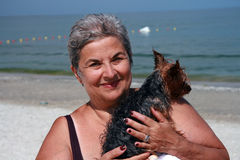 Woman Holding Dog on Beach. Smiling 60 year old woman holding a Yorkshire terrier on a beach in Romania royalty free stock photos