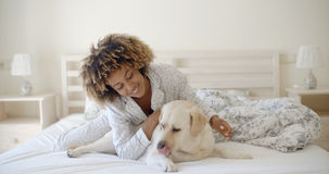 Woman Is Holding A Dog On A Bed Stock Photo