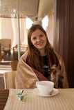 Woman holding a dog in the cafe. Young smiling woman covered with brown blanket sitting in the armchair in the cafe and holding a small dog Royalty Free Stock Photography