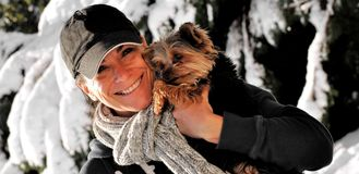 Woman holding a dog in the snow. A middle-aged attractive woman wearing a scarf and hat, holding a small dog in a winter, snow background Stock Photography