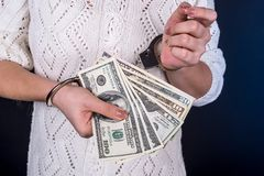 Woman holding dollar bills in handcuffs.  Stock Image