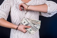 Woman holding dollar  in handcuffs. Woman holding dollar bills in handcuffs Stock Photos