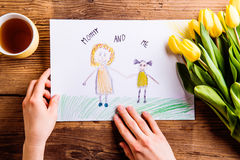Woman holding drawing of her and her daughter. Tulips. Stock Photos