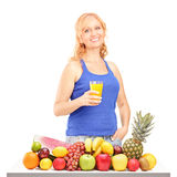 Woman holding a drink in front of pile of fruit Royalty Free Stock Photos