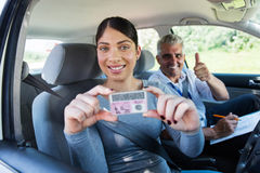 Woman holding driver's license. Pretty women has passed her driving test and holding driver's license royalty free stock photos
