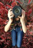 Woman Holding Dslr Camera Sitting on Red Leaved Plant Royalty Free Stock Photo