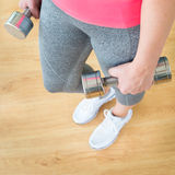 Woman holding dumbbells Stock Image