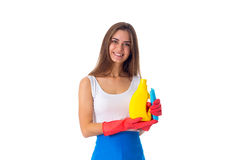Woman holding duster and detergent. Nice young woman in white shirt and blue apron with red gloves holding duster and detergent on white background in studio Royalty Free Stock Photos