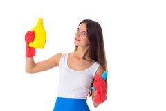 Woman holding duster and detergent. Pretty young woman in white shirt and blue apron with red gloves holding duster and detergent on white background in studio Royalty Free Stock Photography