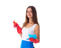 Woman holding duster and detergent. Young attractive woman in white shirt and blue apron with red gloves holding duster and detergent on white background in Stock Images