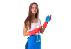 Woman holding duster and detergent. Young beautiful woman in white shirt and blue apron with red gloves holding duster and detergent on white background in Royalty Free Stock Images
