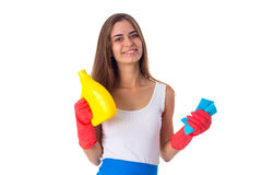 Woman holding duster and detergent. Young charming woman in white shirt and blue apron with red gloves holding duster and detergent on white background in studio Royalty Free Stock Images