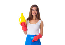 Woman holding duster and detergent. Young good-looking woman in white shirt and blue apron with red gloves holding duster and detergent on white background in Royalty Free Stock Images