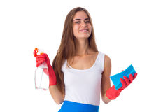 Woman holding duster and detergent. Young happy woman in white shirt and blue apron with red gloves holding duster and detergent on white background in studio Stock Images