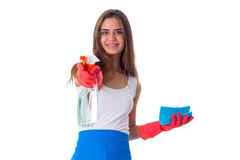 Woman holding duster and detergent. Young positive woman in white shirt and blue apron with red gloves holding duster and detergent on white background in studio Royalty Free Stock Image